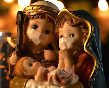 Christmas nativity scene with delicate figures in the new normal of the coronavirus or covid-19. Jose and Maria with chinstraps. Classic Christmas scene lit by candles. Selective focus.